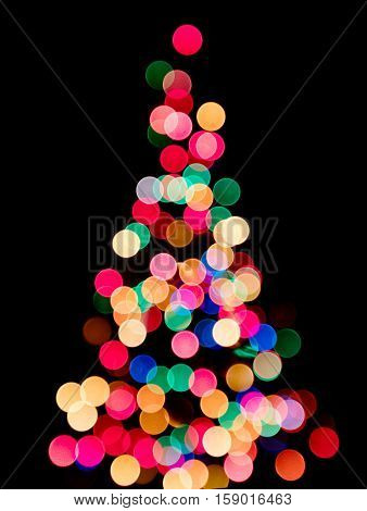 Blurred colorful lights as a silhouette of Christmas tree on black