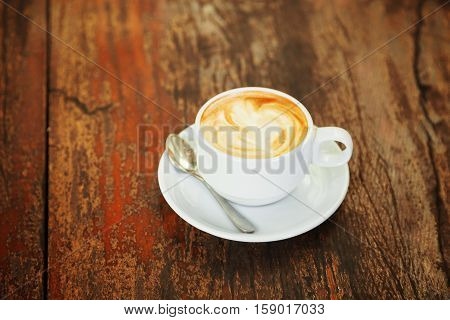 Hot art Latte Coffee in a cup on wooden table