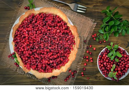 Appetizing cowberry pie and fresh berries cowberry on wooden background top view