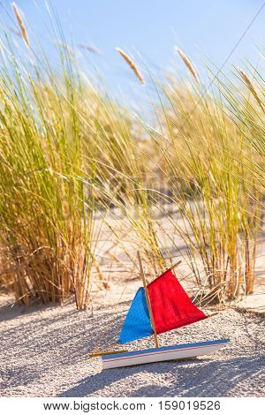 Coastal landscape with dune grass and old toy boat with red and blue colored sails in the sand
