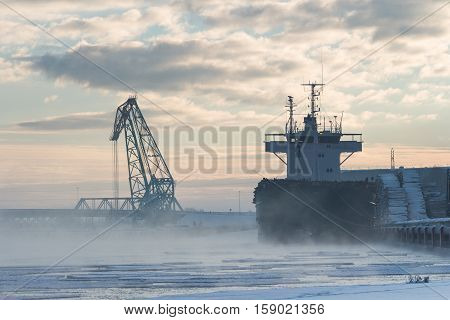 Beautiful foggy winter industrial lanscape. Bulker in a Harbour, loading wood.
