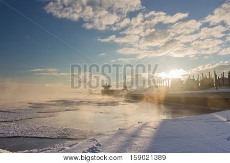 Beautiful winter industrial lanscape. Bulker in a Harbour, loading wood.