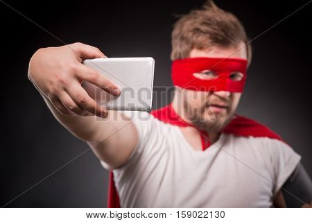 Egoist. Self. Hero. Super Hero. Picture of super hero man wth red mask on making photos on mobile or smart phone in studio.