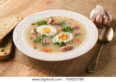 Traditional polish white borscht - zurek, sour soup with white sausages and eggs.