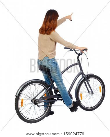 back view of pointing woman with a bicycle. cyclist sits on the bike. Rear view people collection.  backside view of person. Isolated over white background. Girl on bike sits pointing where to go.
