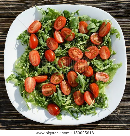 fresh salad with arugula and cherry tomatoes , woden table
