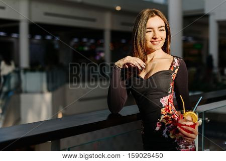 Pretty woman with cocktail in her hand staying in the shopping mall. She wearing elegant dress with deep decollete.