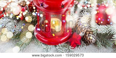 christmas red glowing lantern with decorated evergreen tree and snow on wood with glowing lights banner