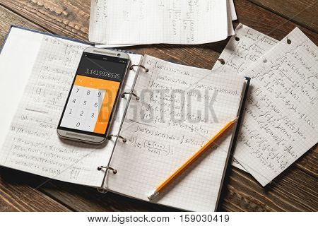 Solving mathematical problems in a notebook .  Phone with calculator app on wooden desk.