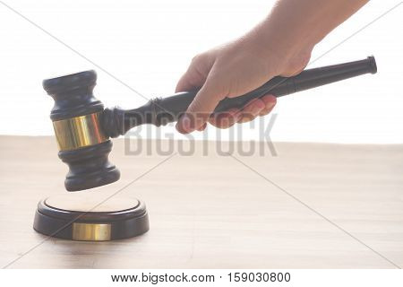 someones hand holding Wooden Law Gavel over wooden table border isolated over white background