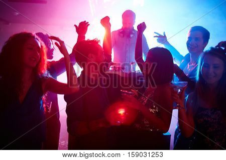 Young couple with drinks and their friends dancing at night party