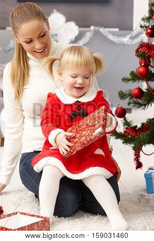 Little girl opening christmas present, sitting on mothers' lap.