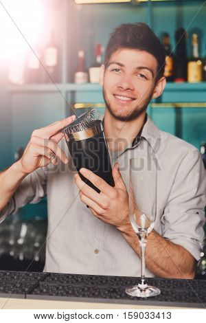 Young handsome barman in bar interior shaking and mixing alcohol cocktail. Professional bartender at work with shaker in hands. Party and nightlife in nightclub. Vertical image