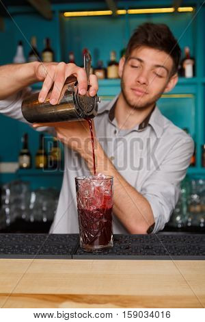 Young handsome barman in bar interior pouring red alcohol to cocktail drink from shaker. Professional bartender at work in night club. Service industry occupation. Vertical image