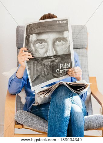 PARIS FRANCE - NOV 29 2016: Woman reading Le Monde newspaper with headline and portrait of Fidel Castro Cuban President - dead on November 25 2016