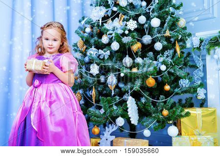 Happy little girl in a beautiful dress standing near the Christmas tree with her gift box. Christmas miracles. Luxurious Christmas decoration.