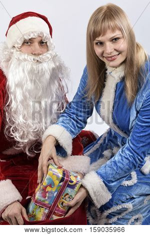 cheerful Santa Claus with the snow maiden holding gifts