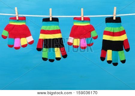 Multicolor striped gloves hanging on the clothesline on blue wooden background
