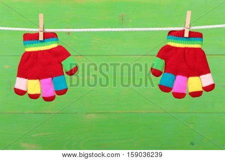 Multicolor striped gloves hanging on the clothesline on green wooden background