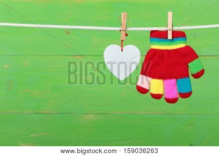 The glove with heart hanging on the clothesline on green wooden background