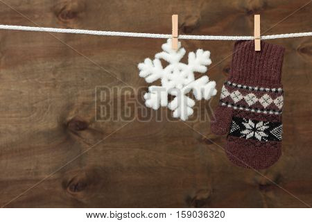 Mitten with snowflake hanging on the clothesline on brown wooden background