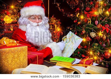 Christmas, mail of Santa Claus. Santa Claus at his home beautifully decorated for Christmas reading letters and making plans of travelling around the planet. Christmas time. Time for miracles.