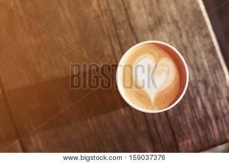 Cup of coffee to go on the wooden table with latte art. Street coffee. Top View.