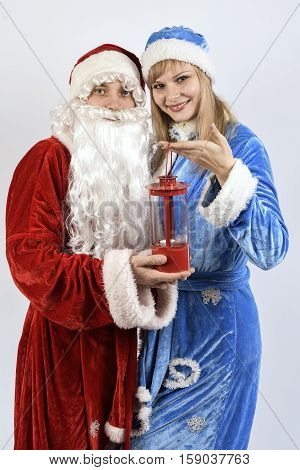 Cheerful Santa Claus with the snow maiden holding a Christmas lamp