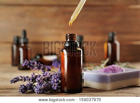 Pipette dropping essential oil into a glass bottle on wooden background