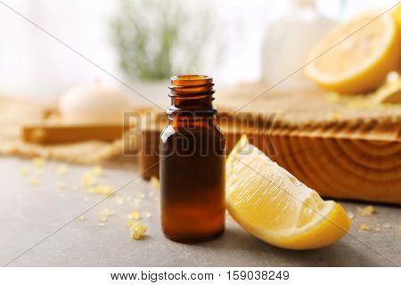 Beautiful spa composition with lemon essential oil on table, closeup