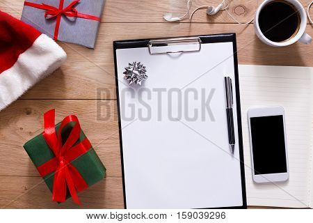 Christmas planning background. Prepare to winter holidays. Top view flat lay of xmas decorations and present, note papers, pen, coffee and mobile phone on wood. Copy space for wishlist or shedule