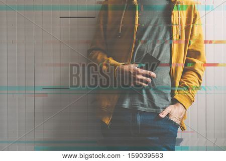 Casual young man posing with mobile phone in hand technology and lifestyle concept retro toned image with digital glitch effect