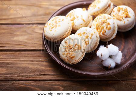Creme brulee macaroons at a ceramic plate and cotton flowers on a wooden table. Soft light. Close view. Space for text