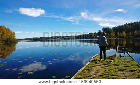 The boy takes a picture of a beautiful lake in autumn sunny day