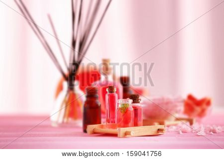 Bottles with essential oil, wooden stand and sea salt on pink table