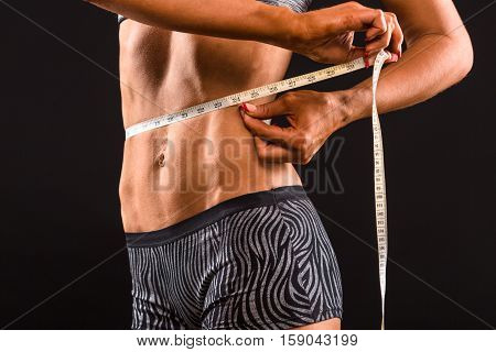 Dieting concepts. Sports woman using meter stick for her body. Fitness lady measuring her waist after or before training in gym in studio.