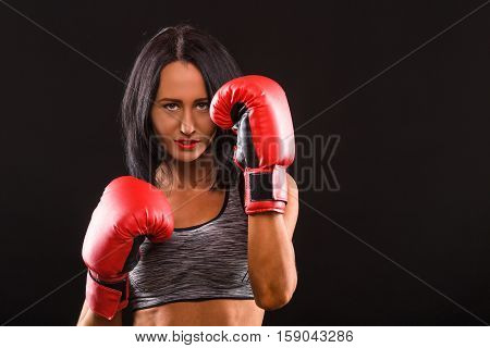 Boxing concept. Young fitness girl with boxing gloves looking at camera over black background.