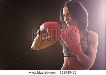 Boxing concept. Boxer woman making direct hit for defense isolated on black. Pretty lady training in gym with red gloves on.