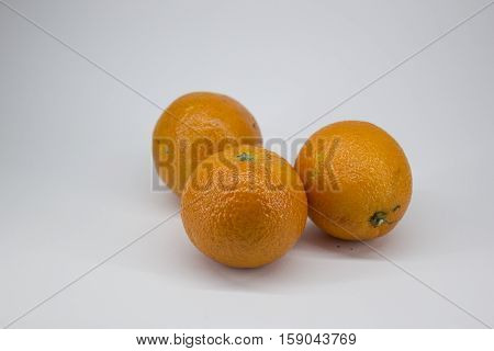 Three ripe tangerines on a white background