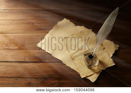 Feather pen with inkwell and blank papers on wooden background