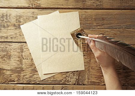 Female hand writing with feather pen and inkwell on wooden background