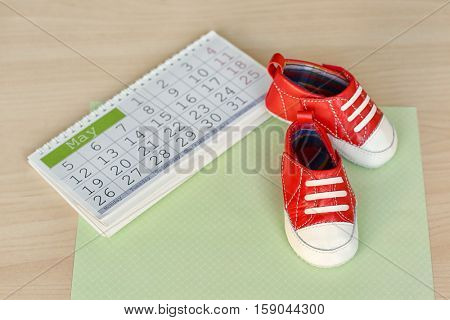 Little baby shoes with calendar on wooden background