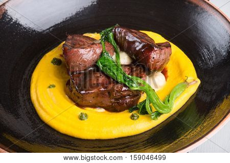 Grilled steak served with yellow garnish humus