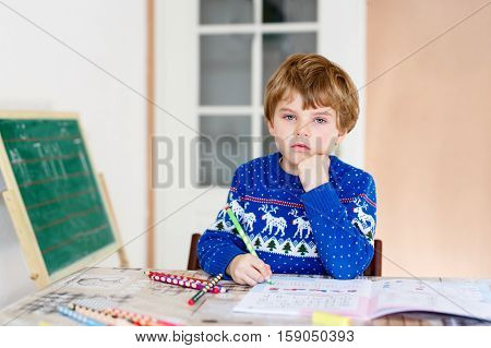 Portrait of frustrated sad school kid boy at home making homework. Little child writing with colorful pencils, indoors. Elementary school and education.