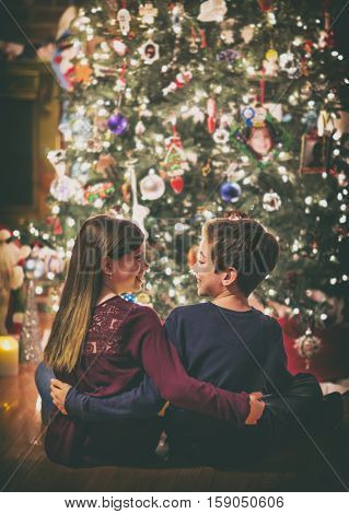 Brother and sister smiling at eachother under a Christmas tree