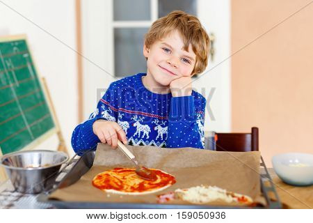 Cute little kid boy making italian pizza with fresh vegetables and tomato sauce and salami in domestic kitchen. Siblings children in colorful shirts having fun with helping at home.