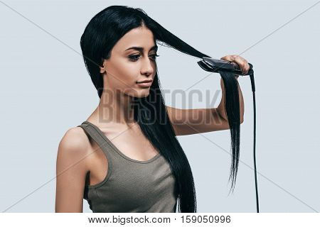Time to make a new hairstyle! Attractive young woman in casual wear styling her long hair with a curling iron while standing against grey background