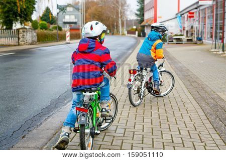 Two active kids boys in helmet biking on bicycles in the city. Happy children in colorful clothes and city traffic. Safety and protection for preschool kids. Friends making sports, acitve leisure.