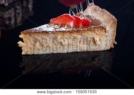 Piece of cheese cake isolated on a blackbackground