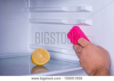 Hand and lemon cleaning refrigerator, sponge in hand